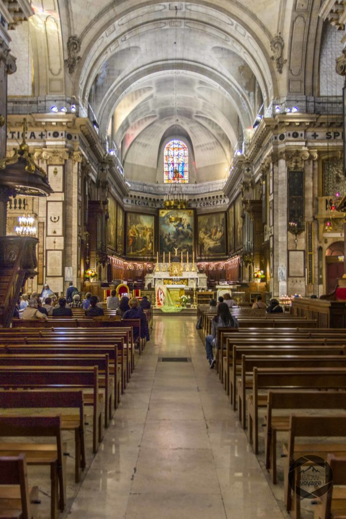 Altar of the Notre-Dame-des-Victoires Basilica in Paris. People are waitting for the mass