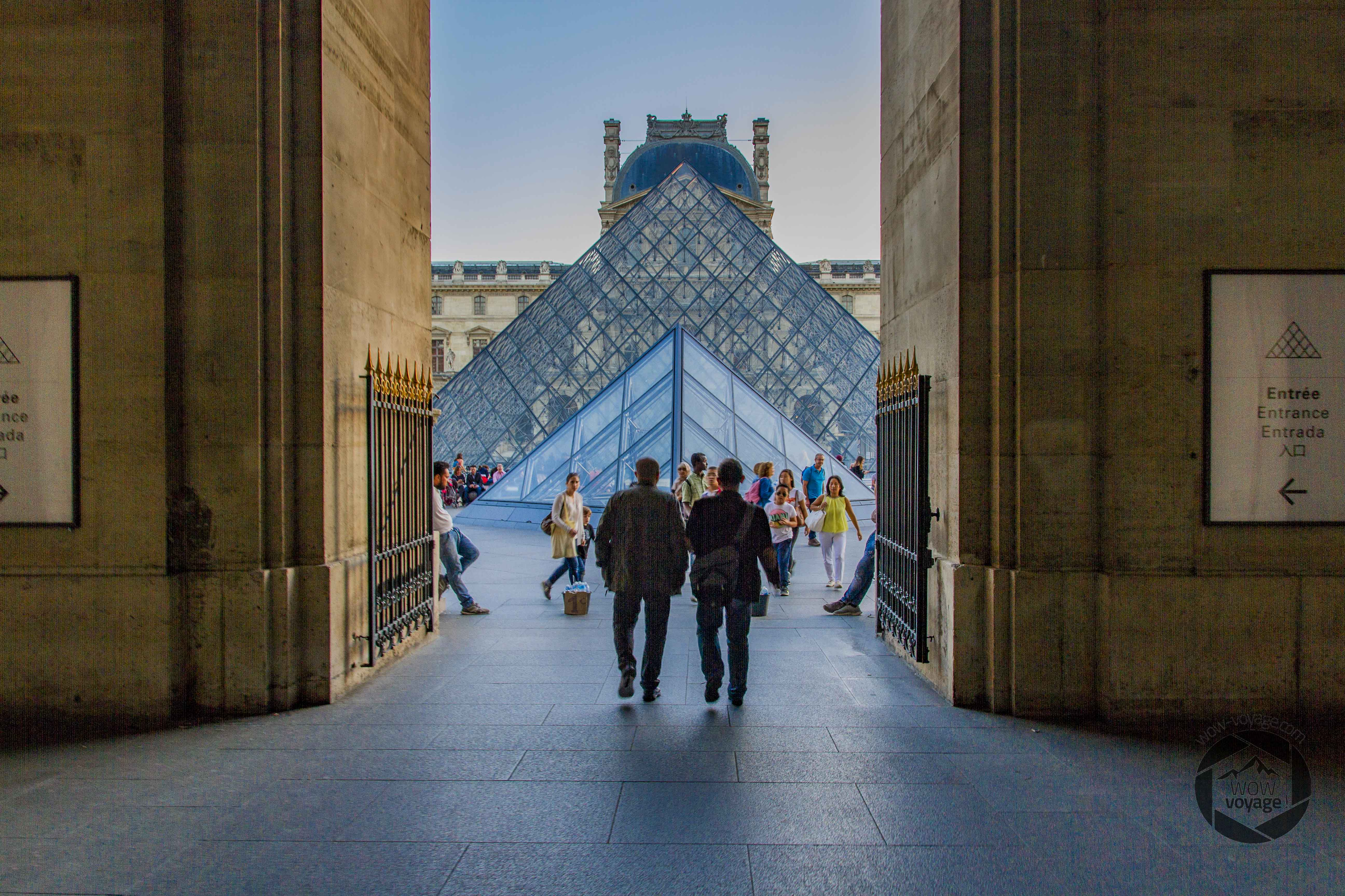 pyramid of the Louvre at sunset People are walking in the street