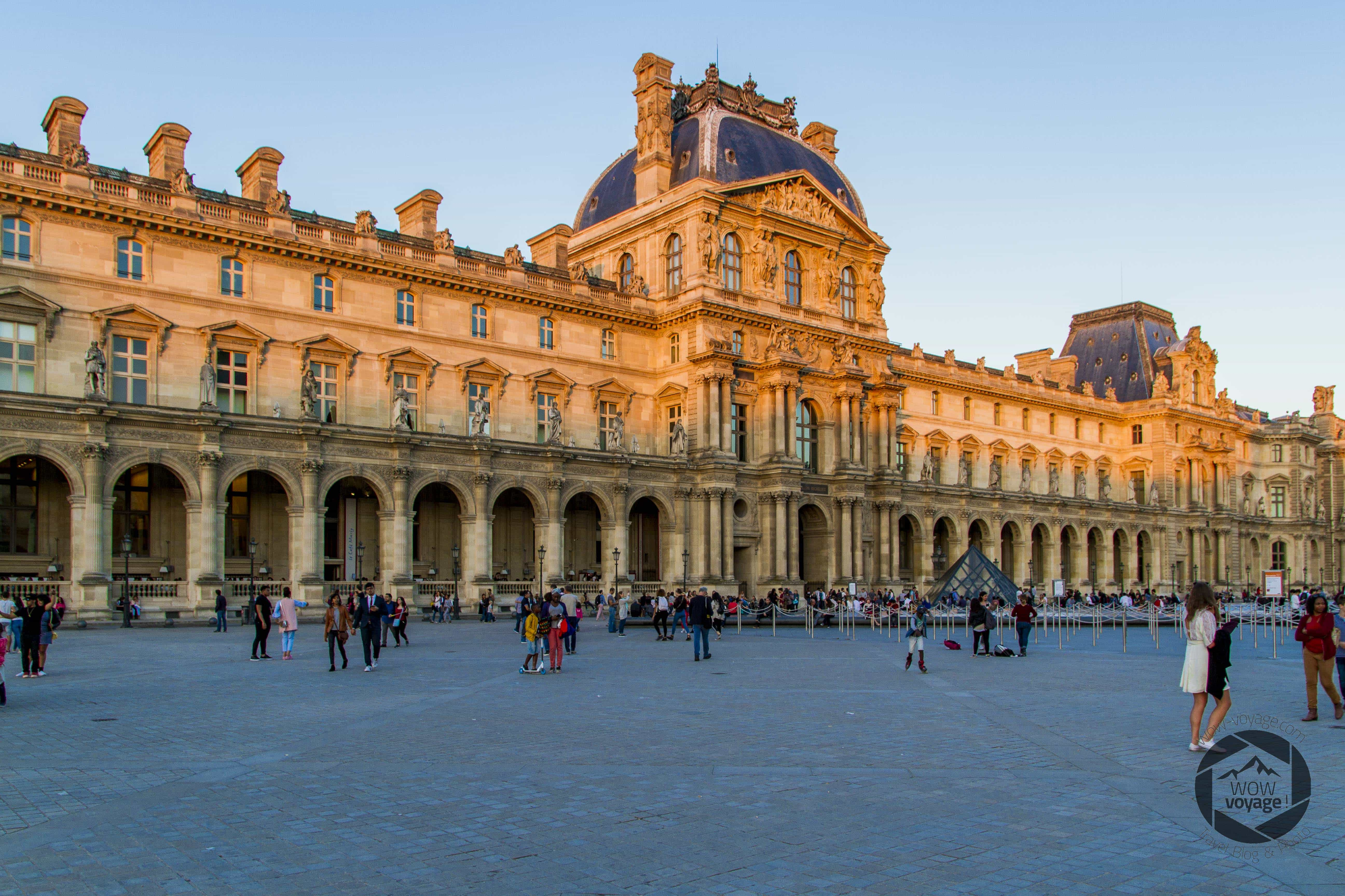 Louvre museum at sunset. People are walking